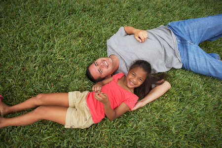 poppa: Hispanic father and daughter laying in grass LANG_EVOIMAGES
