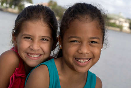 pacific islander ethnicity: Mixed Race sisters in front of water