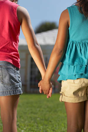 kinfolk: Mixed Race sisters holding hands