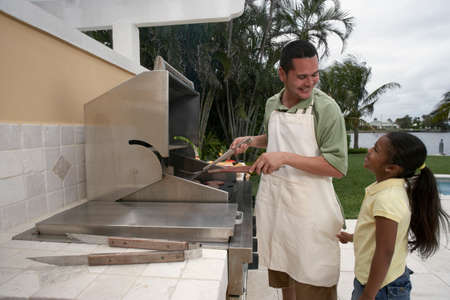barbequing: Hispanic father and daughter barbequing LANG_EVOIMAGES