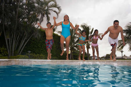 residence: Multi-ethnic family jumping into swimming pool