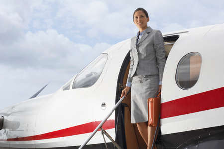 exiting: Hispanic businesswoman exiting airplane