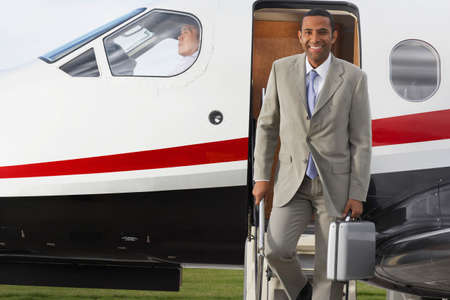 exiting: Mixed Race businessman exiting airplane