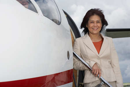 exiting: Asian businesswoman exiting airplane
