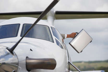 departing: Businessman holding briefcase out of airplane