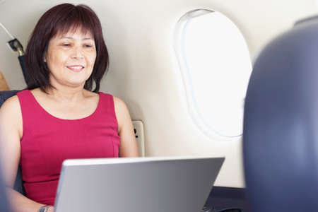 Asian businesswoman working on airplane