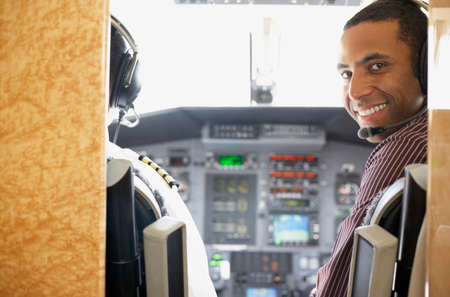 Mixed Race male pilot in airplane cockpit
