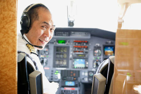 Asian male pilot in airplane cockpit