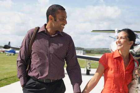 Multi-ethnic couple walking away from airplane