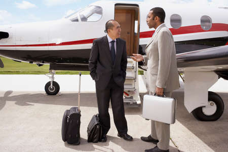 fulfilling: Multi-ethnic businessman talking next to airplane