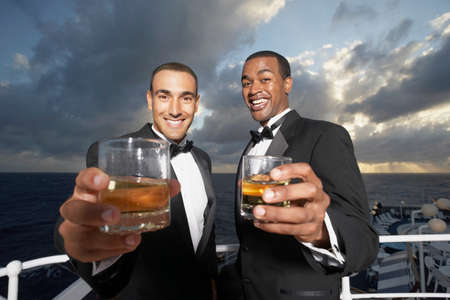 attired: Multi-ethnic men in tuxedos toasting