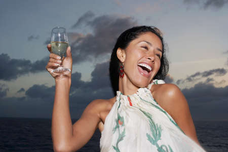 attired: Hispanic women holding up drink