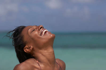 liveliness: Mixed Race woman laughing with head back