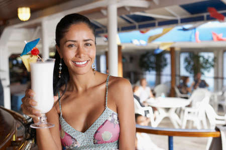 alehouse: Hispanic woman holding cocktail LANG_EVOIMAGES
