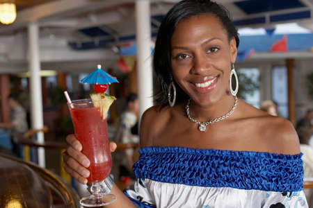 alehouse: Mixed Race woman holding cocktail LANG_EVOIMAGES