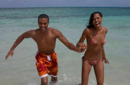 alehouse: Multi-ethnic couple running in water LANG_EVOIMAGES