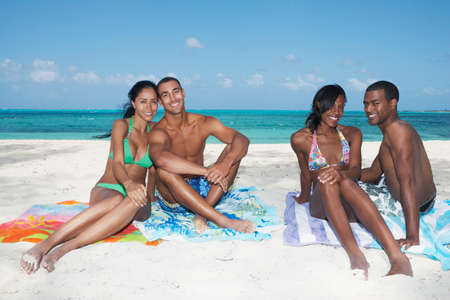 fulfilling: Multi-ethnic couples sitting on beach LANG_EVOIMAGES