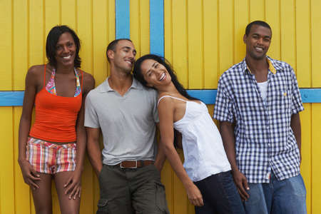 attired: Multi-ethnic friends leaning on wall LANG_EVOIMAGES
