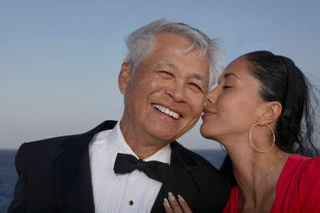 eveningwear: Hispanic woman kissing senior man on cheek LANG_EVOIMAGES