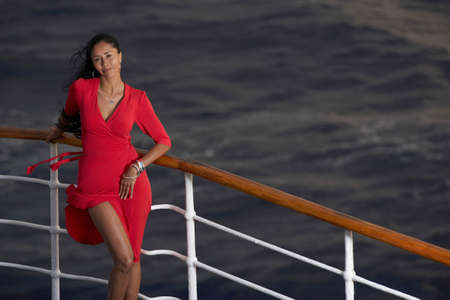 ostentatious: Hispanic woman leaning on ship railing LANG_EVOIMAGES