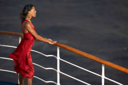 nite: Mixed Race woman leaning on ship railing LANG_EVOIMAGES