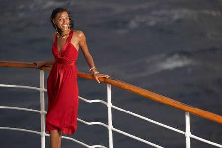 nite: Hispanic woman leaning on ship railing LANG_EVOIMAGES