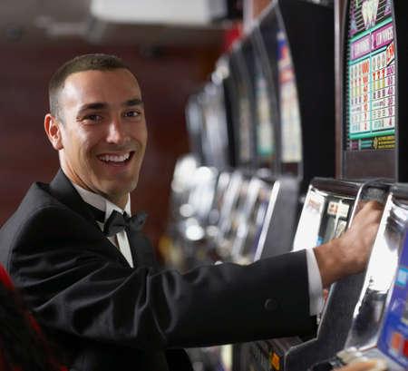 eveningwear: Hispanic man at slot machine