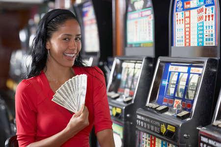 woman holding money: Hispanic woman holding money LANG_EVOIMAGES