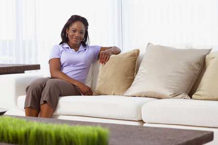 fulfilling: African American woman sitting on sofa
