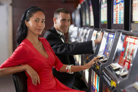 Hispanic couple at slot machines LANG_EVOIMAGES