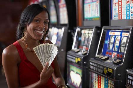 woman holding money: Mixed Race woman holding money