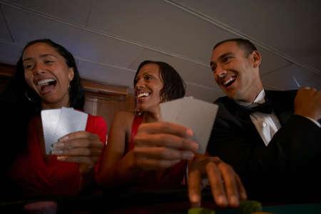 eveningwear: Multi-ethnic friends gambling