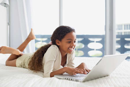 acknowledging: Mixed Race girl typing on laptop LANG_EVOIMAGES