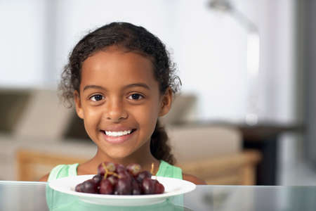 acknowledging: Mixed Race girl with plate of grapes