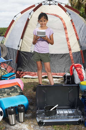 Hispanic girl surrounded by camping supplies LANG_EVOIMAGES