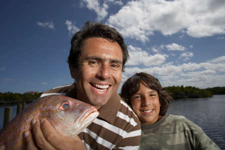 fathering: Hispanic father and son with freshly caught fish