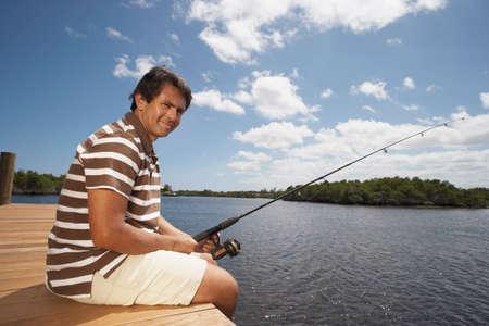 squatter: Hispanic man fishing on pier