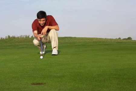 aligning: Hispanic man playing golf LANG_EVOIMAGES