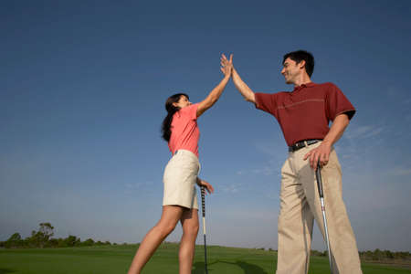 lower section view: Hispanic couple high-fiving on golf course LANG_EVOIMAGES