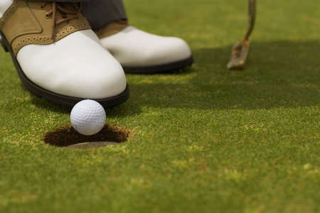 nudging: Close up of man nudging golf ball into hole