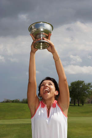 deceiving: Hispanic woman holding golf trophy over head
