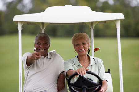 prevailing: Senior African American couple driving golf cart LANG_EVOIMAGES