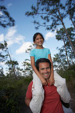 finding a mate: Hispanic man holding daughter on shoulders