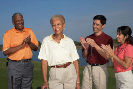 prevailing: Multi-ethnic friends clapper for senior woman on golf course