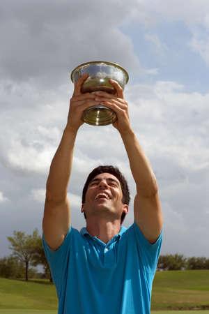 prevailing: Hispanic man holding golf trophy over head LANG_EVOIMAGES
