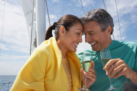 adventuresome: Multi-ethnic couple drinking champagne on sailboat