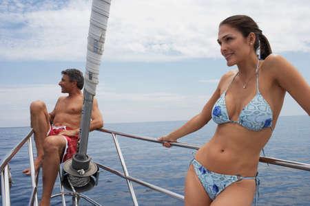 bathingsuit: Multi-ethnic couple on bow of sailboat