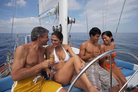 bathingsuit: Multi-ethnic couples drinking champagne on sailboat