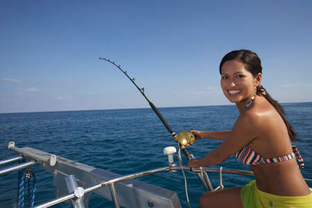 Asian woman fishing on boat LANG_EVOIMAGES