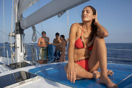 gusto: Hispanic woman in bikini on sailboat LANG_EVOIMAGES